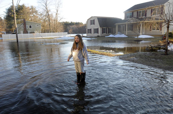 Anna Huddart, 11, stands in the middle of Secret Lake Road in front of her home, as the water begins to recede back into the lake.