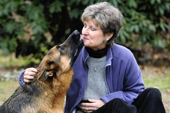 Brave gives owner Susan Selden an affectionate lick in their backyard in Niantic.  Brave had one of his back legs amputated after it became dislocated due to a genetic condition.