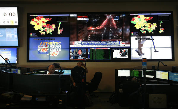 The Los Angeles Fire Department dispatch center with electronic maps of the city as well as television station broadcasts on the wall behind the dispatchers on December 07, 2012. In the event of a major occurrence, the dispatchers can watch TV helicopter coverage to help broaden their understanding of the situation.