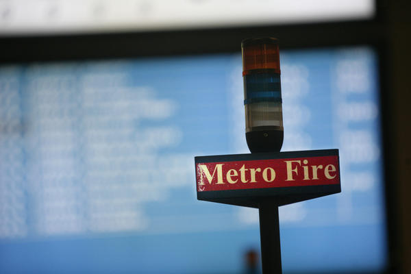 A Metro Fire sign hovers over the desks of dispatchers at the Los Angeles Fire Department Dispatch Center.