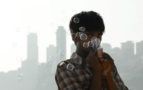 An Indian street vendor, who called himself Tun Tun and makes a living by selling soap bubbles, stands on a popular beach near high rises in South Mumbai on December 10, 2012. People worldwide are celebrating Human Rights Day today.