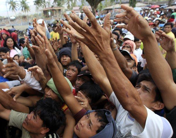 Filipino residents beg for relief goods at an evacuation center in the typhoon-devastated town of New Bataan, Compostela Valley in the southern Philippines on Sunday.