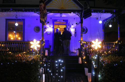 Holiday lights illuminate and welcome folks at the first stop on the Havre de Grace Candlelight Tour, the home of William and Gay Lynn Price at 200 S. Stokes St., as folks make their way inside Sunday evening.