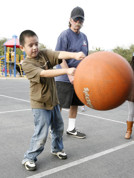 Jacob Marroquin, 6, is being taught how to play punch ball by ASD supervisor Lynn Lehman at McKinley Elementary School in Burbank during the After School Daze city run after-school program on Tuesday, December 4, 2012. The $60,000 program could be cut or restructured next fiscal year.
