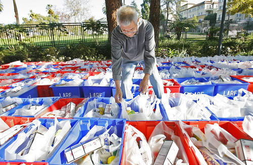 Tino Gutierrez, of Eagle Rock, arranges the handles of the bags with groceries so they are easier to grab at the Pasadena Senior Center where more than 600 came to receive holiday food packages in Pasadena on Friday, December 7, 2012. A bag of food, that includes staples like peanut butter, rice, cheese and cereal, also had a fresh chicken that was provided by San Marino, and a fresh vegetable.