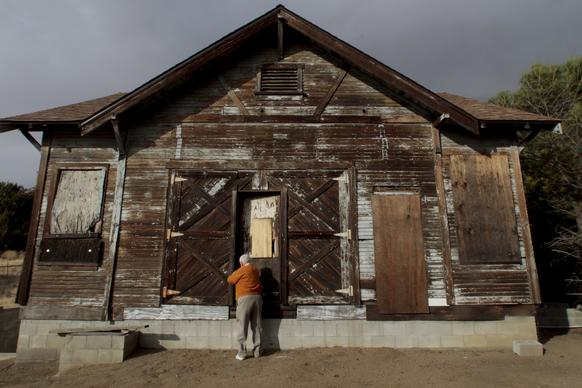 John Seymour of the West Antelope Valley Historical Society unlocks the Old Leona Valley Schoolhouse. Built a century ago, its inside is gutted, but its floor plan and design remain mostly intact.