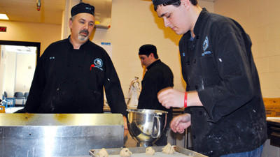 Culinary Arts instructor Bill Geisweidt and student Ed Norton prepare cookies at Greater Johnstown High School last week. About 400 dozen cookies are being shipped to troops in Afghanstan.