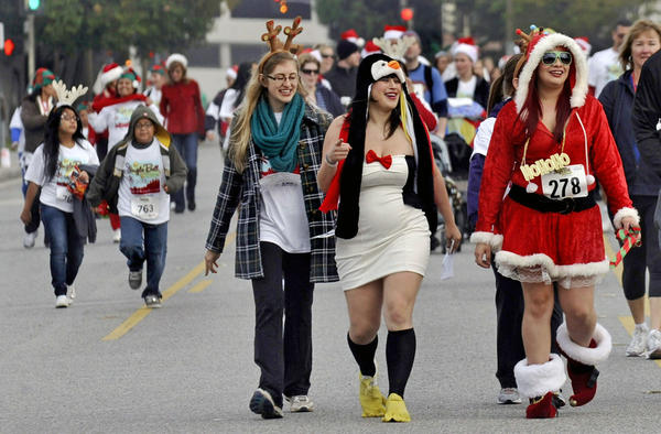 Runners and walkers in holiday costumes head south on Orange St. during the Arthritis Foundation's Jingle Bell Run/Walk for Arthritis through the streets of downtown Glendale on Sunday, December 9, 12012.