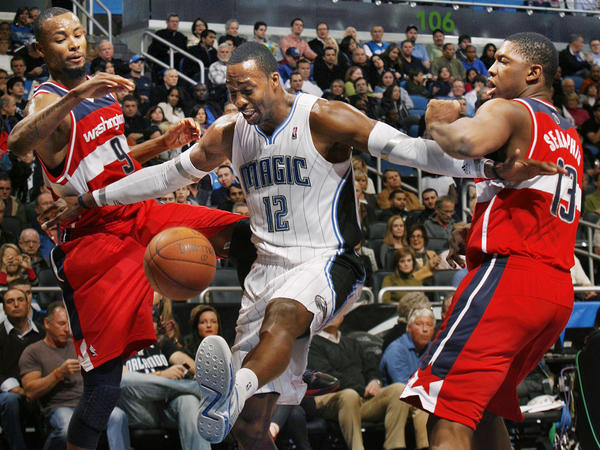 Orlando center Dwight Howard kicks the ball as he shoves away Washington forward Rashard Lewis (9) and Washington forward Kevin Seraphin (13) during the Washington Wizards at Orlando Magic NBA game at the Amway Center on Wednesday, January 4, 2012. Orlando won the game 103-85.