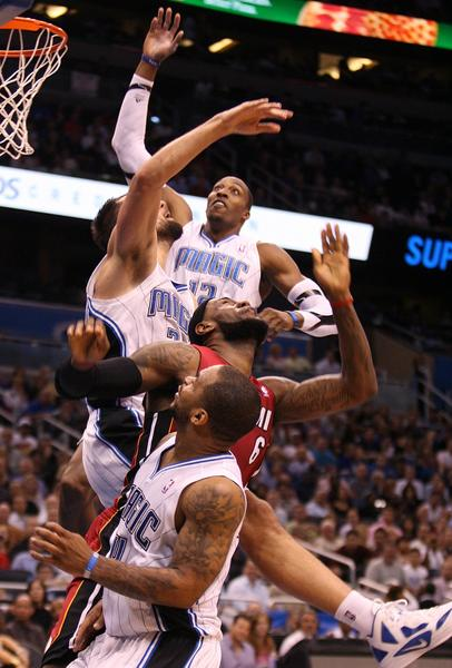 Orlando center Dwight Howard, top, Miami forward LeBron James (6), Orlando forward Ryan Anderson, left, and Orlando guard Jameer Nelson (bottom) collide during the Miami Heat at Orlando Magic NBA game at the Amway Center in Orlando, Florida, Tuesday, March 13, 2012.