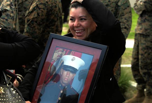 Sonya Cazarez, mother of Marine Cpl. Robert Cazarez, smiles as she carries his portrait after his family received his posthumous certificate of citizenship in a ceremony at Camp Pendleton on Dec. 6.