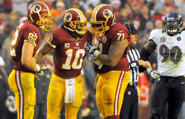 Redskins tight end Logan Paulsen (82) and tackle Trent Williams (71) assist quarterback Robert Griffin III (10) after a sack in the fourth quarter Sunday.