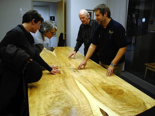 Wilmette Village Forester Kevin Sorby, right, explains shows off a new conference room table made from the Bicentennial Ash tree, which fell during a 2011 windstorm.
