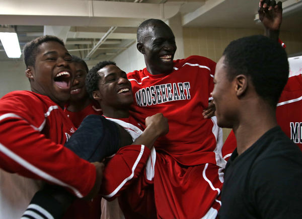 In wake of the IHSA's ruling that he, along with Sudanese teammates Akim Nyang and Mangisto Deng, are eligible to play, Mooseheart's Makur Puou is lifted up by teammates in the visiting locker room at Hiawatha High School in Kirkland, Ill.
