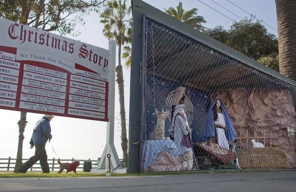 A woman walks her dog along the dirt path behind the Nativity scene at Pacific Palisades Park along Ocean Avenue in 2011.