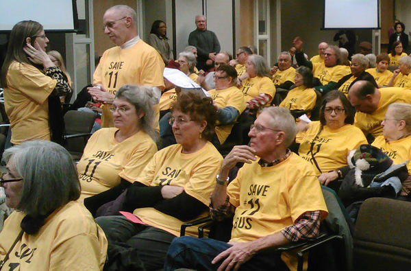 "Wearing matching t-shirts that read ""Save #11 bus"" on the front and ""It's our lifeline!"" on the back, people attend the CTA budget hearing on Monday."