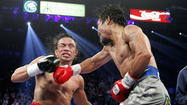 Juan Manuel Marquez of Mexico takes a punch from Manny Pacquiao of the Philippines during their welterweight fight at the MGM Grand Garden Arena