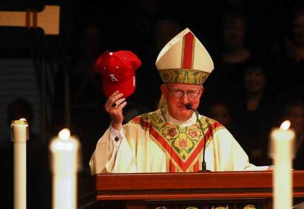 Bishop Kevin W. Vann holds up a Los Angeles Angels of Anaheim baseball cap during his speech to congregants at his installation as the new bishop of the Diocese of Orange County. The ceremony took place at the Bren Events Center in Irvine.