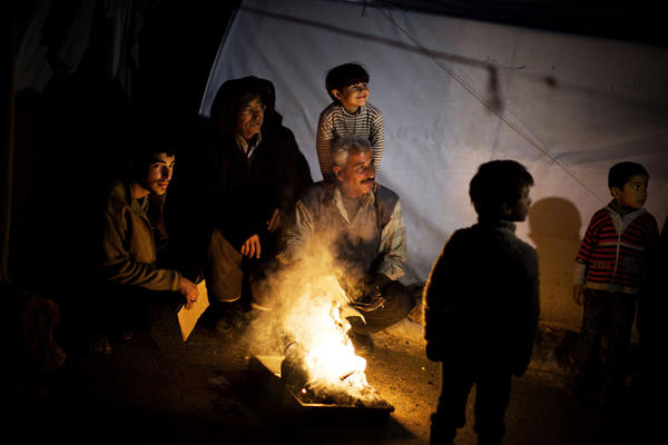 Syrian men make a fire to boil water Sunday near their tent at a refugee camp near the Turkish border in Azaz, Syria.