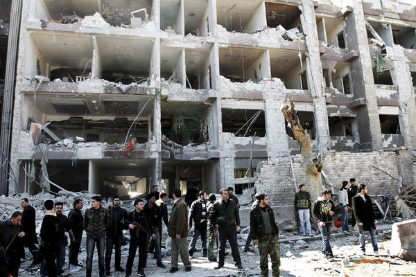 Syrian security officers gather March 17 in front of the damaged building of the aviation intelligence department, which was hit by one of two explosions in Damascus. Jabhat al-Nusra claimed that it carried out the double suicide bombing.