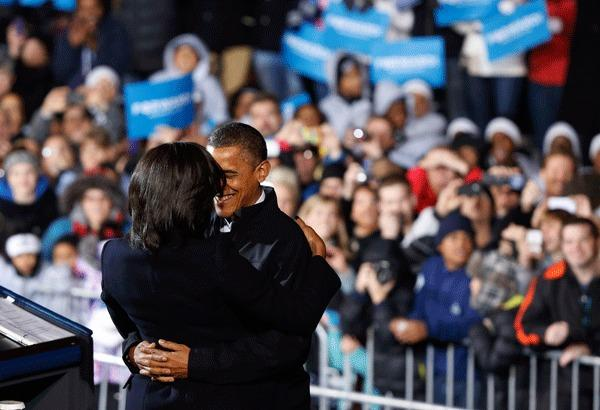 U.S. President Barack Obama hugs First Lady Michelle Obama before he addresses supporters on last night of campaign in a downtown Des Moines, Iowa, rally, November 5, 2012.