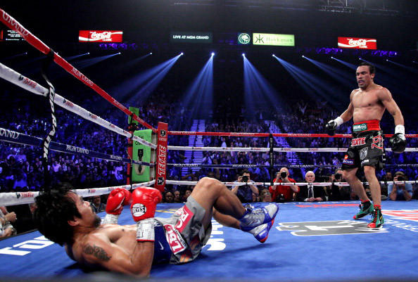 Manny Pacquiao (L) falls to the canvas after being knocked down by Juan Manuel Marquez in the 3rd round of their welterweight fight.