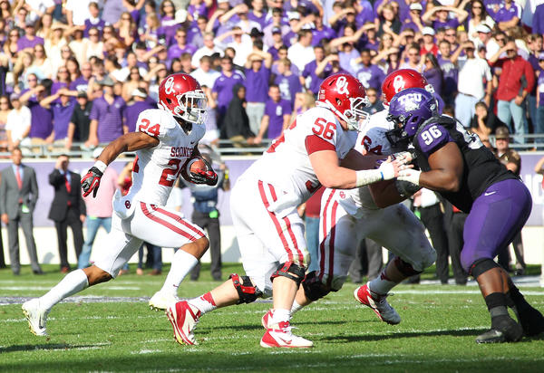 Brennan Clay #24 runs the ball as Ty Darlington #56 of the Oklahoma Sooners blocks Chucky Hunter #96 of the TCU Horned Frogs at Amon G. Carter Stadium on December 1, 2012 in Fort Worth, Texas.