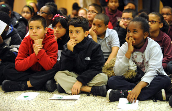 4th graders (from left) Steve Rosado, Jovanni Cruz, and Raven Bristow listen intently to Director of Pastoral Care at Sacred Heart Hospital Father John Hilferty as he tells Sacred Heart Elementary students the Christmas story. The hospital held their Tree of Life Celebration Tuesday afternoon in the lobby of the hospital. Each ornament on the trees they lit had a name attached and were bought in memory of people no longer with us. Students from Sacred Heart Elementary School attended and participated in the event.