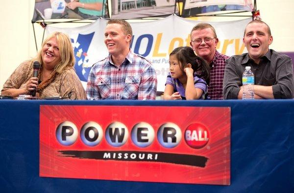 Cindy Hill, left, with her son Jason, daughter Jaiden, husband Mark and son Cody laugh during a news conference at North Platte High School in Dearborn, Mo., after the family claimed half of a $587.5 million Powerball lottery jackpot.