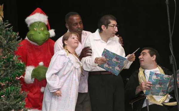 "BCR Adult Day Program clients' Karlee Songstad, Ricky Salcedo and Dennis Poulson, with the Grinch and staff Jay Bogan, singing ""You're a Mean One, Mr. Grinch."""