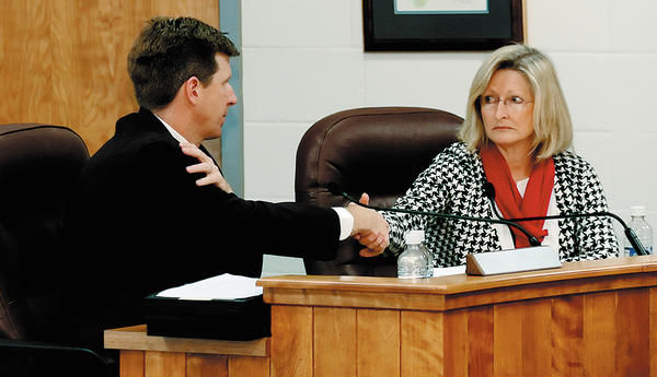 Donna Brightman shakes hands with Justin Hartings after he was voted president of the Washington County Board of Education. Hartings had four votes, Brightman had three.