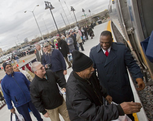 Coach Attendant Clifford Brown helps guests board a train car for a tour following a ceremony to mark new Amtrak service in Norfolk. Public service begins from the Norfolk station on Wednesday morning.