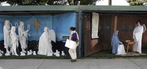 A woman, seen here in December 2011, walks past two of the Nativity displays that for 60 years had been put up in Palisades Park in Santa Monica.