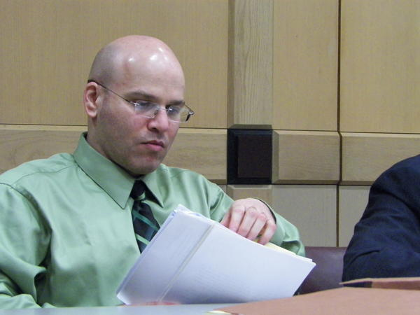 Seth Penalver reviews court papers while his lawyer, Hilliard Moldof, addresses jurors Tuesday. Penalver faces the death penalty if convicted of three June 1994 murders.