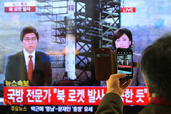 A South Korean man in Seoul photographs a televised report on the launch.