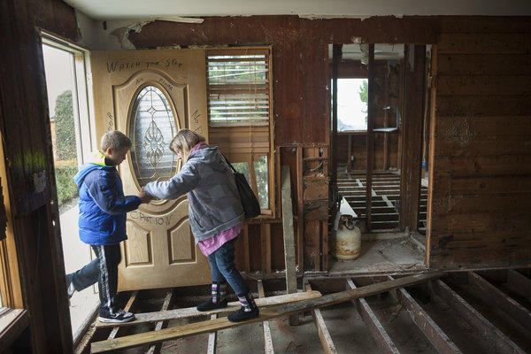 Lori Rebimbas helps her son, Nick, 9, onto a board placed across the remains of the floor of their Point Pleasant, N.J., home, which was badly damaged by Superstorm Sandy.