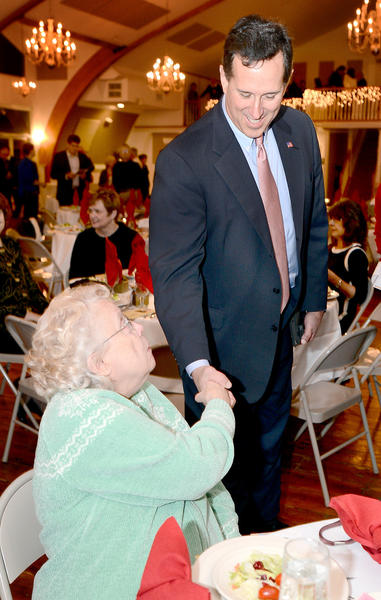Former U.S. Sen. Rick Santorum shakes hands with Carol Myers of Thurmont, Md., Tuesday night at Green Grove Gardens in Greencastle, Pa.