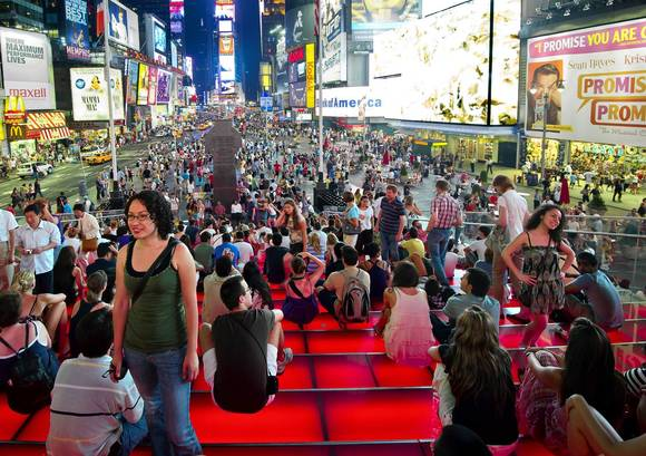 People on the red stairs on Times Square at night.