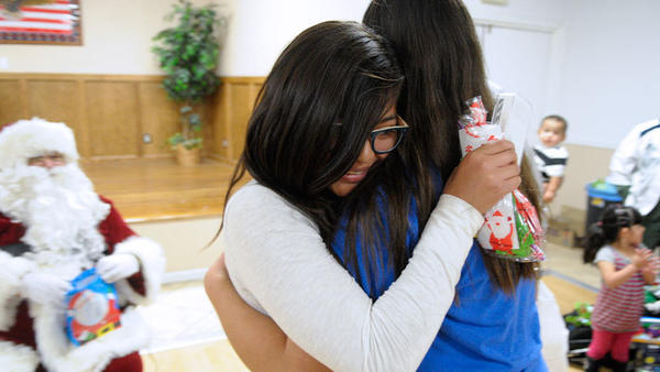 Hannah Hunter, 12, is hugged after giving away her own iPod to another 12-year-old during the Centinela State Prison gift exchange for the Center for Family Solutions at the Eagles Lodge in El Centro.