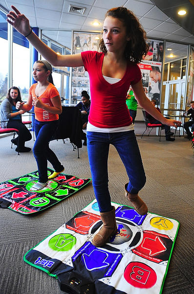 Tina Martinez, right, and her sister, Teri Martinez, left, play a dance video game Tuesday afternoon at the Waynesboro (Pa.) Area YMCA as part of the YMCA's 12 Days of Christmas celebration. Tuesday's 12 Days activities focused on games and contests for teens who come to the YMCA after school.