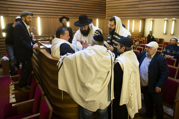 An infant boy is surrounded by rabbis and relatives at a Jewish ritual circumcision ceremony in Berlin in October.