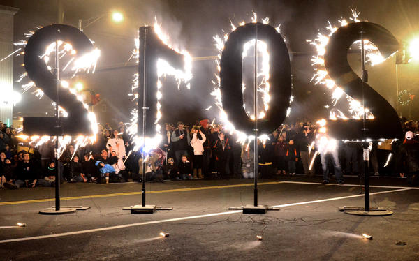 With eyes to the skies, revelers watch the fireworks from near the corner of Washington and Main Streets in Middletown in front of a sparkler-lit 2012 sign.