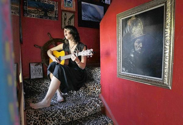 Emily Satterlee, a 27-year-old Orange Coast College student, sings a song she wrote at her friend's home in Huntington Beach on Tuesday. Satterlee is raising money for her first professionally produced album on IndieGoGo.