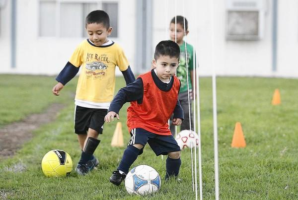Marcos Ramos, 4, Ethan Avila, 5, center, and Leonardo Aguillar, 5, back, participants in the Oak View Youth Soccer League, run through drills on Friday.