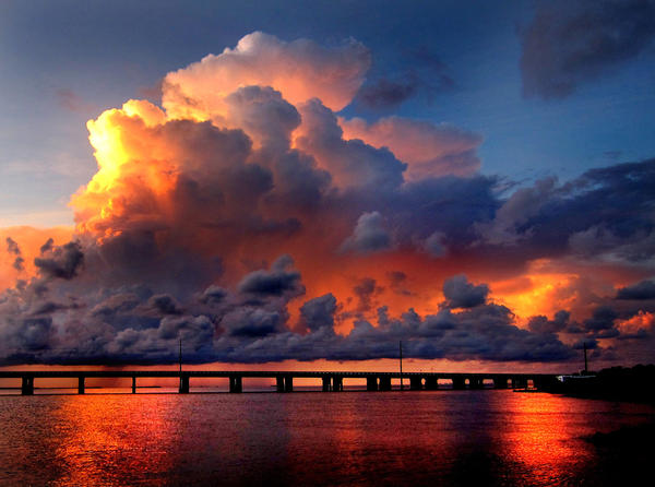 Storm clouds provide a dramatic scene at sunset at the Bahia Honda bridge, in this view from the bayside of  Bahia Honda State Park, near Big Pine Key, Fla., Saturday, August 4, 2012.