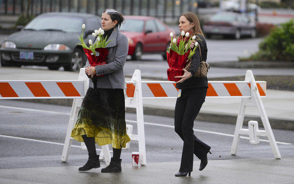 Leslie King, left, and Tenille Beseda carry flowers to place at the entrance of the Clackamas Town Center Mall in Clackamas, Ore., where a shooting killed two victims and left a third seriously injured.
