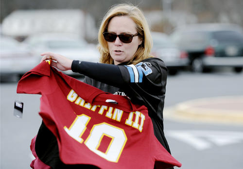Ilana Bittner, of Columbia, shows off her Redskins Robert Griffin III jersey for the cameras at the Wayne Curry Sports and Learning Center in Landover on Wednesday, Dec. 12. This was one of the options Howard County Executive Ken Ulman had to wear while picking up trash after losing a bet to Prince George's County Executive Rushern Baker on the Redskins/Ravens game Sunday.