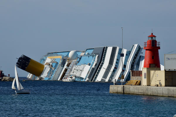 This file photo taken on June 25 shows a small dinghy sailing past the stranded Costa Concordia cruise ship near the harbor of Giglio Porto. The Concordia cruise ship disaster left 32 people dead amid accusations of a series of safety breaches and fatal delays.