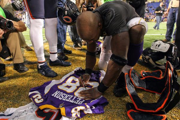 Minnesota Vikings running back Adrian Peterson (28) signs a jersey for Chicago Bears wide receiver Brandon Marshall (not pictured) following the game at the Metrodome.