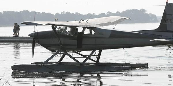 Spectators watch from a dock as a seaplane taxis in Lake Dora during the Seaplane Fly-in at the Tavares Seaplane Base in Wooton Park on Saturday, April 28, 2012. (Stephen M. Dowell/Orlando Sentinel)